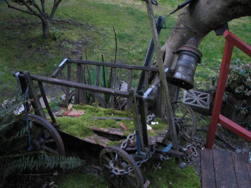 This dilapidated cart is chained to a gnarled tree in the yard.