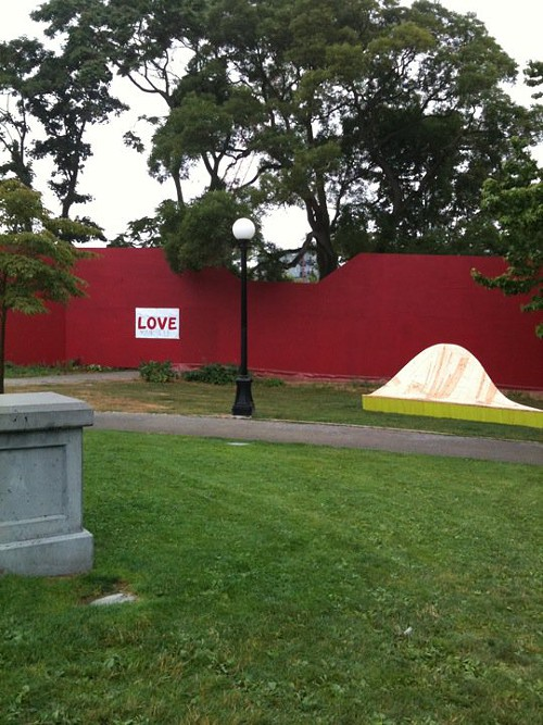 The love sign and the red construction wall arent part of Alex Haydens sculpture, but they sure add to the scene.