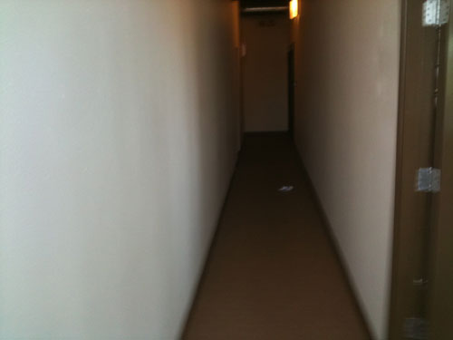 Empty hallway with beer can.