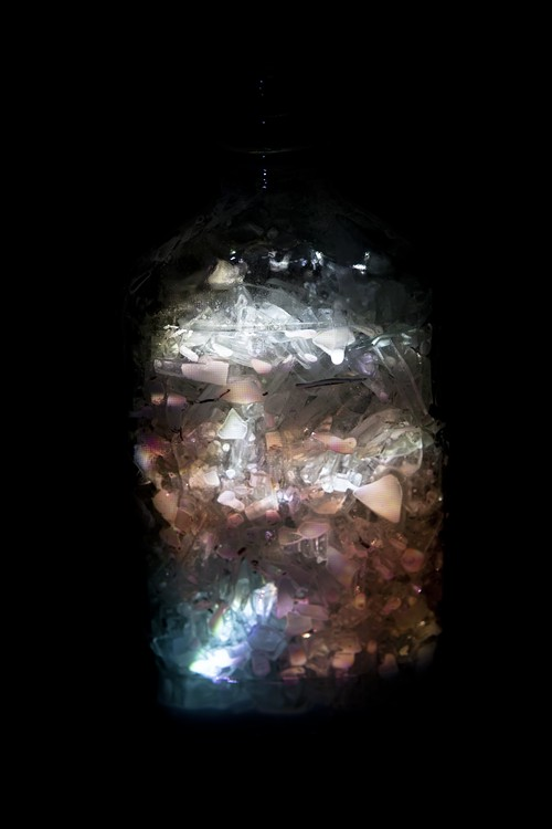 To create this photograph, Leif Anderson he filled a whisky bottle with glass shards, poured in paint and shook the bottle, then projected onto it the image of a smoking man he once met.