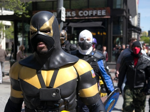 Ben Fodor, a.k.a. Phoenix Jones arrives with a posse of dudes in body armor and masks. Jones told me Occupy was cool, but that he doesnt see the point in vandalizing banks. He said theyre out to protect people and property.   Hopefully people hug a tree, break out some banjos, play some bluegrass music and everyone goes home, said another masked man, who asked to be identified only as Boomer. But this is Seattle, so thats not going to happen.