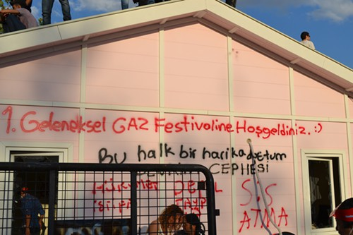 Pre-fab buildings set up by the construction company in Gezi Park are ransacked on Saturday.  Graffito: Welcome to the first annual gas festival.