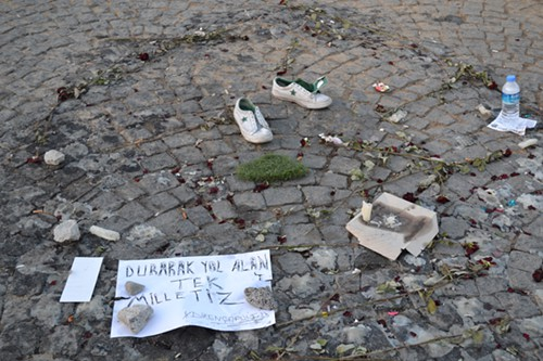 """Pairs of shoes left in conspicuous places have become memorials to the fallen. Sign: """"We are the only nation gaining ground by standing."""""""