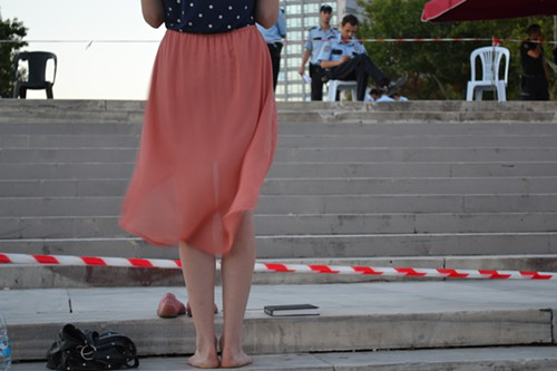 A barefoot young woman in a standing protest on the Gezi Park steps.