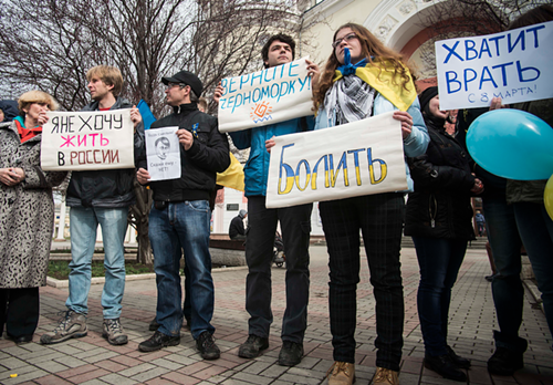 Ukrainians and Tatars rally against Russian aggression in Simferopol—the man in black is holding a drawing of Putin with Hitlers mustache and slicked hair.