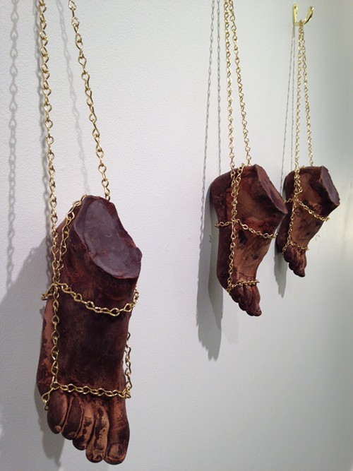 These feet are made of chocolate. Dark-toned feet in chains. Intentionally uncomfortable or just uncomfortable? Or do you see jewelry? By Sabe Lewellyn at Gallery 110.