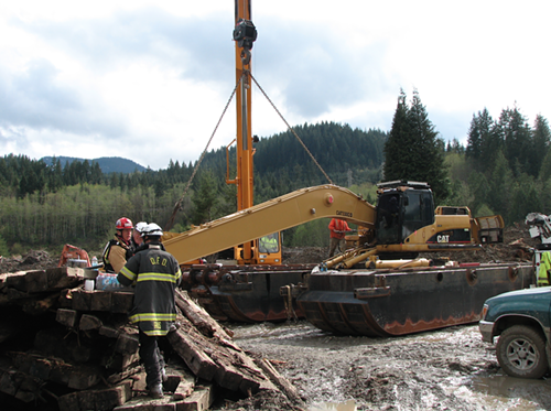 Guys talking near an enormous pontoon excavator, which can excavate in swampy conditions.