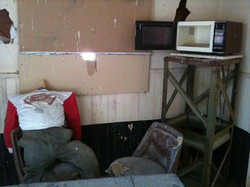 A living room/kitchen used for target practice, just sitting out in the desert.