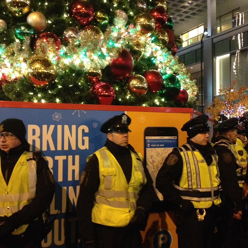 A ring of police defending the Christmas tree. Ten feet away, circle of protesters chanting, No justice no peace and Shut it down!