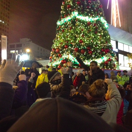Now, a silent protest in front of the tree. Men in black hoods shout at shoppers, Enjoy your slave labor goods! and Go run up your credit cards! Other protesters shush them.