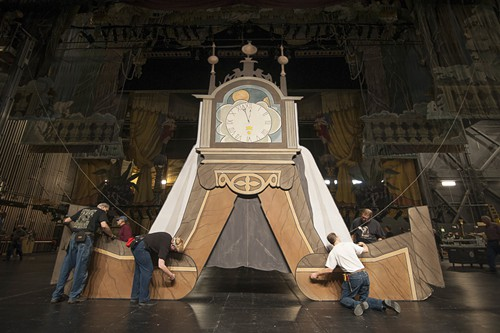 """Stagehands dismantle one of two clocks—a small one and a large one—that appear in the show. Maurice Sendak had designed the production from his house, alongside visiting PNB artists, and the set was built over three months in seven different cities. Tucker said that when Sendak came out to see the first production being assembled, he saw the small clock and said: """"Jesus, that's huge! Where's the small clock?"""" Randall G. """"Rico"""" Chiarelli, PNB's resident lighting designer, smiled and said: """"That <em>is</em> the small clock."""""""