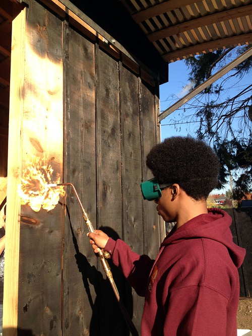 Students used an old Japanese technique of burning cedar to finish a shed at the Judkins P-Patch.