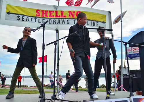 Aji Piper (center), president of the local Plant for the Planet chapter, dances with his brother and sister to an adaptation of Uptown Funk with lyrics about climate change and the oil industry.