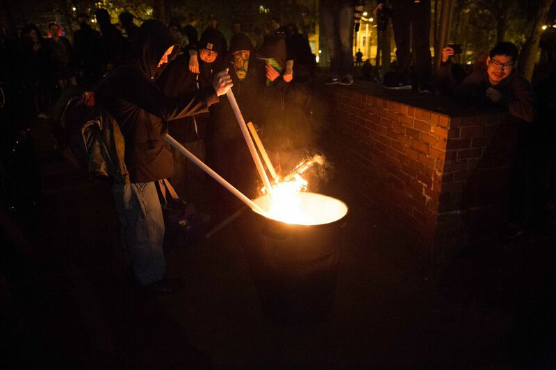 Protesters setting fire to a trash can.