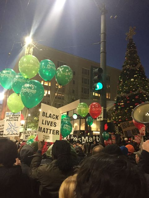 People are tying protest signs to holiday balloons at Westlake.