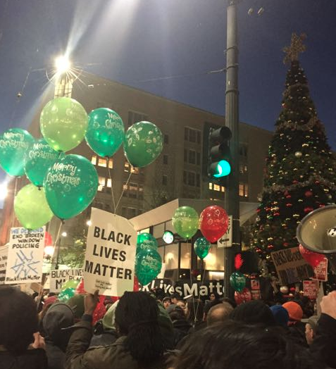 A crowd of several hundred protesters was on the move this afternoon in downtown Seattle, marching through the streets around Westlake Plaza, entering Macys, and trying to enter Westlake Mall and Pacific Place. The Seattle Police Department has reported two arrests, and the protesters made their presence known at the annual Christmas tree lighting ceremony.