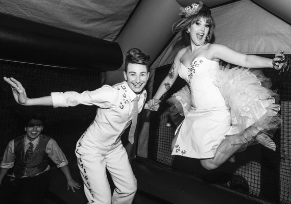 """That's Lou on the left and Kitten on the right, better known as the burlesque/dance/drag duo """"Kitten N' Lou.""""  They're pictured here jumping up and down in a bouncy castle, which they set up for their wedding reception. Galvin said this wedding was perhaps the most fun wedding she'd ever attended, mostly because it featured a fucking bouncy castle."""