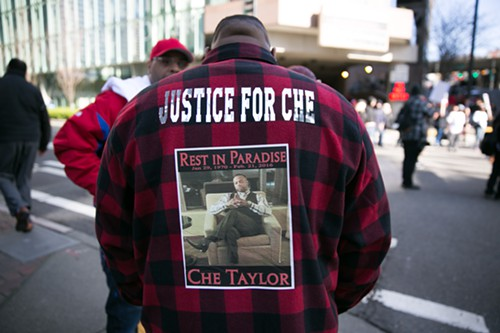 A friend of Che Taylor stands near the demonstration in front of Seattle Police HQ