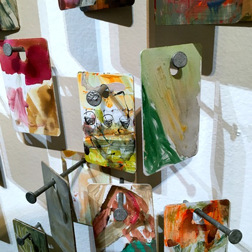 An installation of Gabriel Jesiolowskis tiny paintings mounted to the wall on construction nails at The Alice.