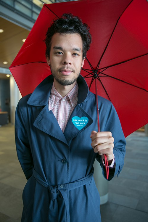 A demonstrator holds a red umbrella in city hall as a petition is delivered to city council members